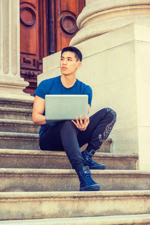 Young Asian American College Student studying in New York City, wearing blue T shirt, black pants, sneakers, sitting on stairs in office building on campus, working on laptop computer, thinking.