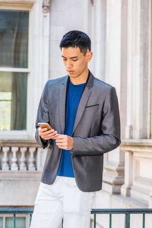 Young Asian American College Student texting on cell phone inside office building in New York City, wearing gray blazer, blue undershirt, white pants, standing on campus, holding cell phone, reading.