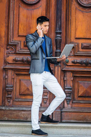 Multiple task. Young Asian American Man studying, working in New York, wearing gray blazer, white pants, black shoes, standing by old office door, working on laptop computer, talking on cell phone. Stockfoto