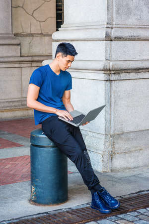Young Asian American College Student studying, working in New York City, wearing blue T shirt, black pants, sneakers, sitting on pillar on street on campus, looking down, working on laptop computer.