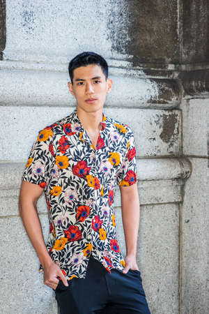 Young Man Summer Casual Street Fashion. Portrait of Young Asian American College Student in New York City, wearing sort sleeve, colorful flowers patterned shirt, stranding against wall in corner. Stockfoto