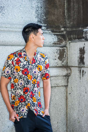 Young Man Summer Casual Street Fashion in New York City. Young Asian American College Student wearing sort sleeves, colorful flowers patterned shirt, stranding against wall in corner, looking away.