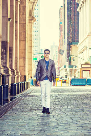 Young Asian American Man traveling in New York, dressing in gray blazer, white pants, black shoes,  wearing sunglasses, earphones, listening music, walking through old narrow street in sunny day.