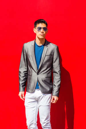 Portrait of Young Asian American Man in New York City, dressing in fashionable gray blazer, blue undershirt, white pants, wearing blue sunglasses, standing against red background under sun, looking. Stockfoto