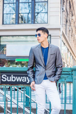 Young Asian American Man traveling in New York, dressing in gray blazer, white pants, wearing sunglasses, earphones, listening music, standing on street by Subway sign, looking around, waiting.