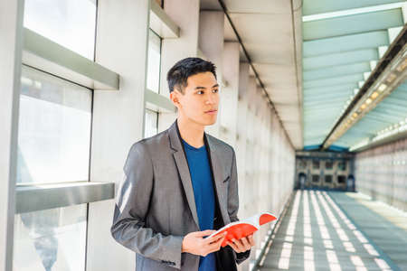 Young Asian American College Student studying in New York, wearing gray blazer, blue shirt, standing on walkway against glass wall on campus, reading red book, looking away, thinking.