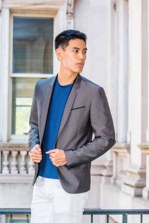 Portrait of Young Asian American College Student in New York City, wearing gray blazer, blue undershirt, white pants, standing in old fashion style office building on campus, looking away. Stockfoto