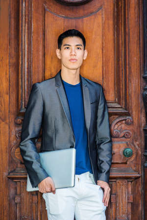 Portrait of Young Asian American Businessman in New York City, wearing in fashionable gray blazer, blue undershirt, white pants, holding laptop computer, standing by brown office door, looking forward Stockfoto - 165415666