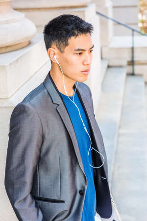 Portrait of Young Asian American College Student in New York City, wearing gray blazer, white earphone, carrying laptop computer, listening music, walking down stairs of old style office building.