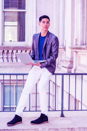 Young Asian American College Student studying in New York City, wearing gray blazer, white pants, black shoes, sitting on railing on campus, working on laptop computer, thinking. Color filtered effect Stockfoto - 165415671