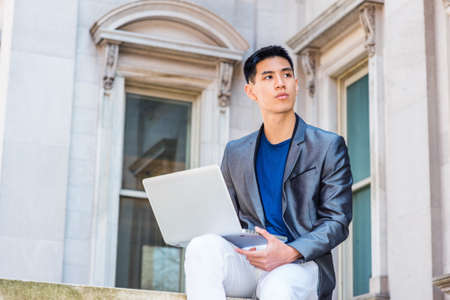 Young Asian American College Student studying, working in New York City, wearing gray blazer, white pants, sitting outside old style office building on campus, reading on laptop computer, thinking.