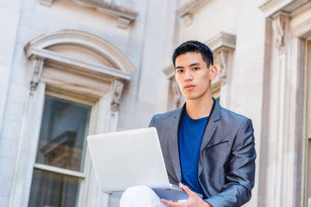 Young Asian American College Student studying, working in New York City, wearing gray blazer, sitting outside old style office building on campus, reading, working on laptop computer, thinking.