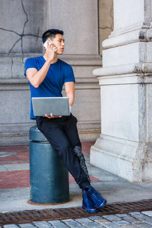 Young Asian American College Student studying in New York City, wearing blue T shirt, black pants, sneakers, sitting on pillar on street on campus, working on laptop computer, talking on cell phone.