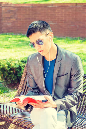 Young Asian American Man traveling, studying in New York City, dressing in gray blazer, white pants, wearing white earphone, blue sunglasses, sitting on bench, listening music, reading red book. Stockfoto - 165415684
