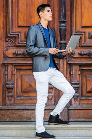 Young Asian American College Student studying, working in New York City, wearing gray blazer, white pants, black cloth shoes, standing by old style office door, working on laptop computer, thinking.