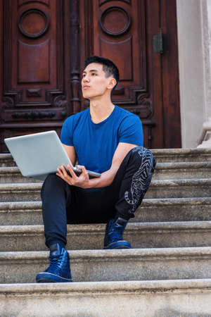 Young Asian American College Student studying in New York City, wearing blue T shirt, black pants, sneakers, sitting on stairs in office doorway on campus, working on laptop computer, thinking.