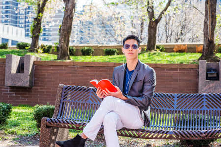 Young Asian American Man traveling, studying in New York City, dressing in gray blazer, white pants, wearing white earphone, blue sunglasses, sitting on bench, listening music, reading red book, Stockfoto