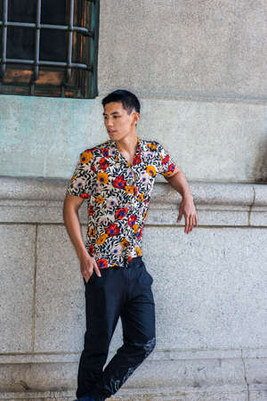 Young Asian American Man thinking outside in New York City, wearing sort sleeves, colorful flowers patterned shirt, black pants, stranding against old style wall on street, looking down, relaxing.