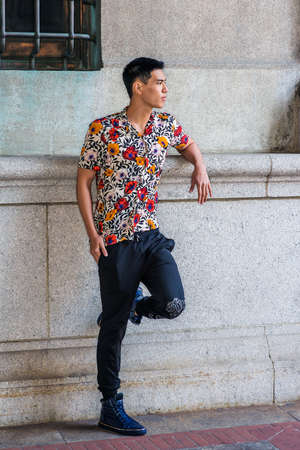 Young Asian American Man relaxing outside in New York City, wearing sort sleeves, colorful flowers patterned shirt, black pants, sneakers, stranding against old style wall on street, looking forward. Stockfoto