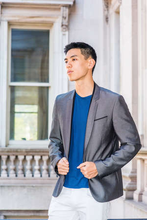 Portrait of Young Asian American College Student in New York, wearing gray blazer, blue undershirt, white pants, standing in old fashion style office building on campus, thinking, lost in thought. Stockfoto