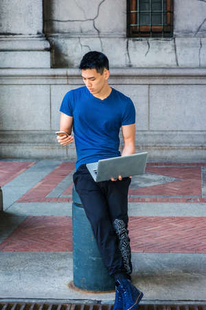 Young Asian American College Student studying in New York City, wearing blue T shirt, black pants, sneakers, sitting on pillar on street on campus, working on laptop computer, texting on cell phone.