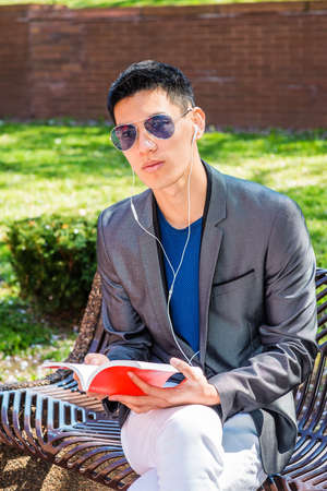 Young Asian American Man traveling, studying in New York City, dressing in gray blazer, white pants, wearing white earphone, blue sunglasses, sitting on bench, listening music, reading red book. Stockfoto
