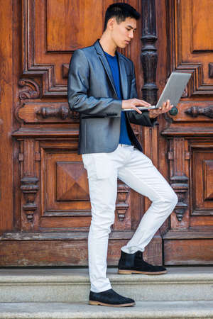 Young Asian American Man studying, working in New York City, wearing fashionable gray blazer, white pants, black shoes, standing by old style office door, looking down, working on laptop computer.