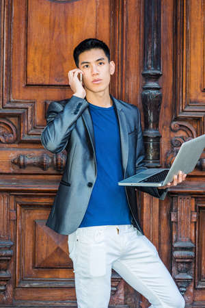 Multiple task. Young Asian American Man studying, working in New York City, wearing gray blazer, white pants, standing by old brown office door, working on laptop computer, talking on cell phone. Stockfoto