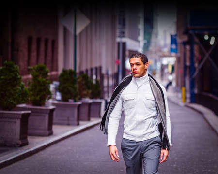 Like the wind, a handsome young man is confidently walking on the old street in New York City. A fine art lifestyle photography