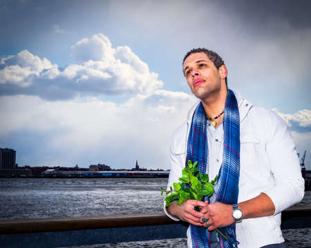 A handsome young man is standing by the river's fence, holding a bunch of green leaves, looking up, hope, thinking, lost in thought. A fine art color photography.
