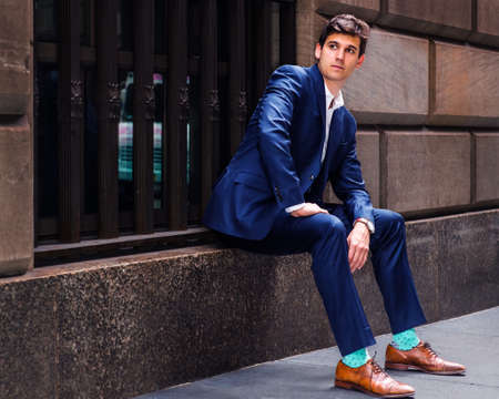 A handsome young businessman travels in New York City, wearing a blue suit, brown leather shoes, light green patterned socks, sitting on a big window frame of an old street, relaxing.