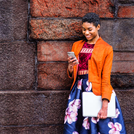 A Young African American Woman is texting on a cell phone outside, wearing an orange, red jacket, a flower-patterned skirt, carrying a laptop computer, standing by a stone wall on campus, smiling.