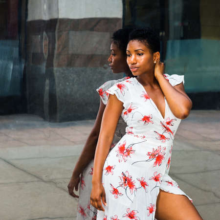 Young African American Woman with a short afro hairstyle, wearing a patterned dress, is standing against a mirror on the street, sad, thinking. Concept of self-assured, self-esteem, self-checking.