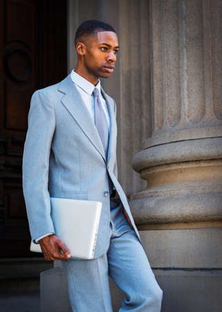 A Young African American Businessman, wearing a light gray suit, a white undershirt, a tie, holding a laptop computer, is walking down from the vintage office building doorway. Stockfoto