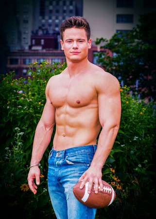 Man's Beauty. Shirtless, half-naked, wearing jeans, a young, strong, sexy man, holding an American football, is standing outside in a big city. A fine art color photography. Stockfoto