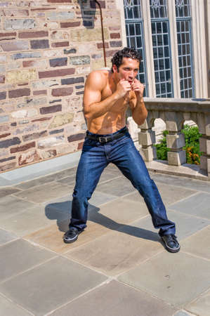 Dressing in jeans and leather sneakers and shirtless, a handsome, muscular guy is waving arms and exercising to counterattack Stockfoto