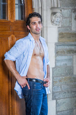 Wearing a cross necklace, with his shirt unbuttoned, a handsome, muscular guy is standing by a old fashion doorway and relaxing.