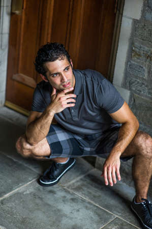 Dressing in a gray shirt, pattern shorts and black leather sneakers, one hand touching his chin,  a young strong handsome guy is squatting in the front of the door, relaxing and thinking.