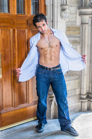 Wearing a cross necklace, opening his shirt, a handsome, muscular guy is standing by a old fashion doorway and cooling down.