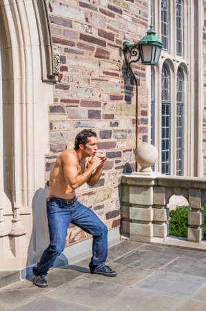 Dressing in jeans and leather sneakers and half naked, a handsome, muscular guy is waving arms and exercising to counterattack