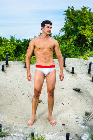 A masculine guy, wearing a white underwear, barefoot, is standing in a abandoned structure, charmingly looking forward.