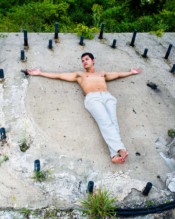 A masculine guy, wearing a white pants, barefoot and half naked, is climbing a slope with the help of metal rods Stockfoto