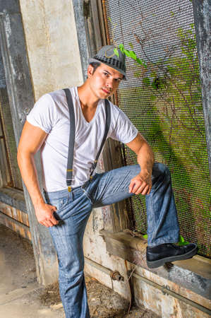Dressing in a white T shirt, blue jeans with suspenders, and a gray fedora hat,  a young handsome guy is standing by a screen window inside a abandoned house,  mysteriously looking at you. Stockfoto