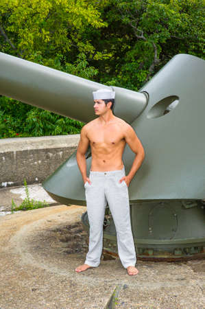 A masculine guy, wearing a marine hat,  a white pants and half naked, is standing by a big gun, looking forward