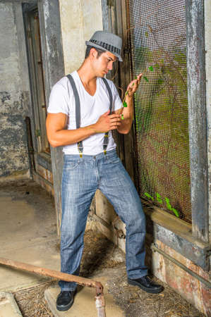 Dressing in a white T shirt, blue jeans with suspenders, and a gray fedora hat,  a young handsome guy is standing inside a abandoned house,  looking at green leaves on hands and into deeply thinking.