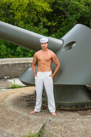 A masculine guy, wearing a marine hat,  a white pants and half naked, is standing by a big gun, thoughtfully looking at you Stockfoto