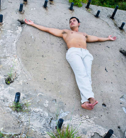 A masculine guy, wearing a white pants, barefoot and shirtless, is stretching arms and lying on a slope wall