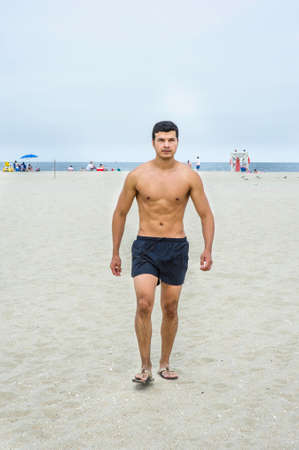A young masculine guy, half naked,  is walking on the beach.