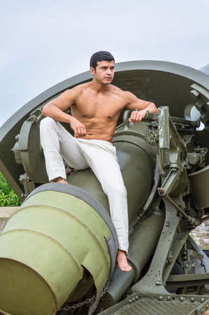 A masculine guy, wearing white pants, barefoot and half naked, is sitting on a big gun, relaxing and thinking.