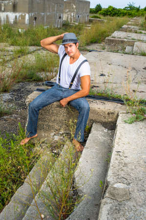 Dressing in a white T shirt, blue jeans with suspenders, wearing a gray hat and barefoot, a young handsome guy is sitting on a desolation land and charmingly looking at you.